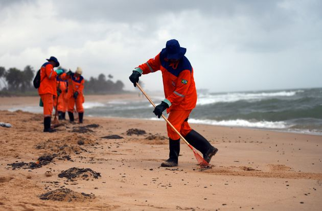 Municipal employees work to remove an oil spill on Barra de Jacuipe beach in Camacari, Bahia state, Brazil,...