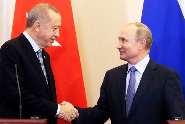 Turkish President Recep Tayyip Erdogan, left, and Russian President Vladimir Putin shake hands during...