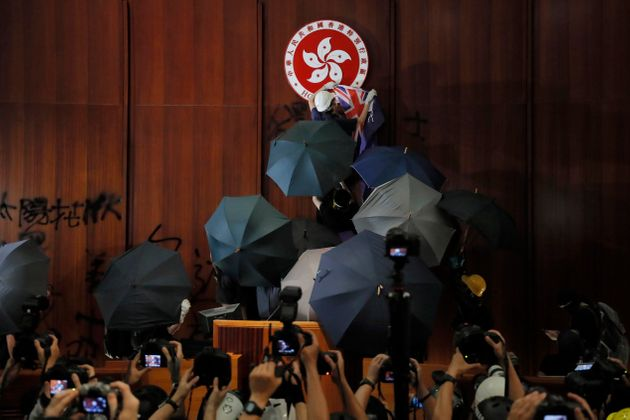 FILE - In this July 1, 2019, file photo, a protester covers the Hong Kong emblem with a Hong Kong colonial...