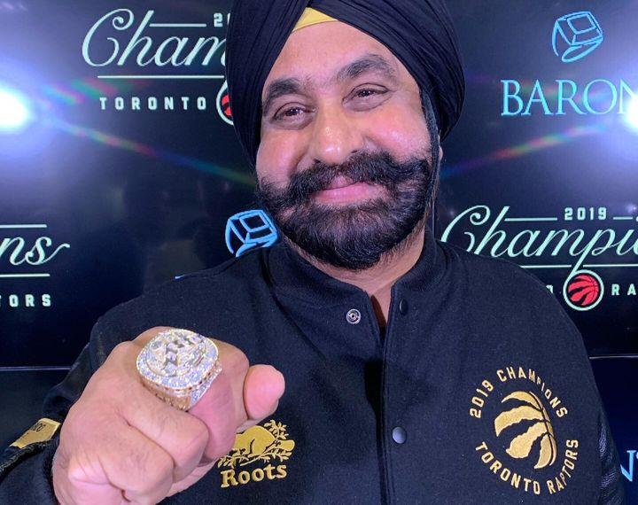 "Toronto Raptors ""Superfan"" Nav Bhatia smiles while posing with his customized NBA championship ring in Toronto on Tuesday."