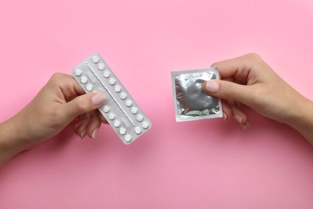 Contraceptive means: a condom and birth control pills in a hand on a pink