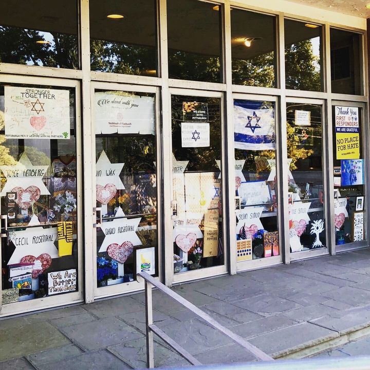 The doors of the Tree Of Life synagogue covered in posters and signs related to the mass shooting.