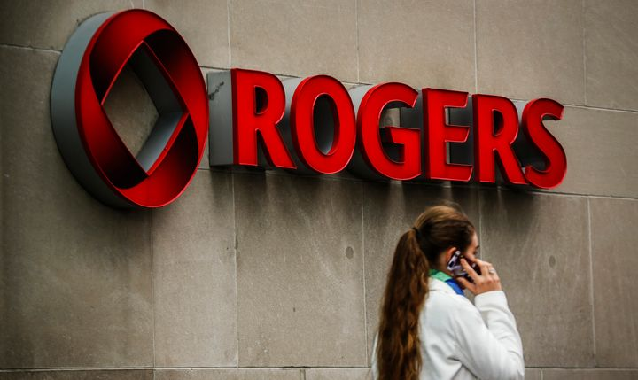 A woman speaks on her cell phone in front of a Rogers sign at the company's annual general meeting for shareholders in Toronto, April 22, 2014.