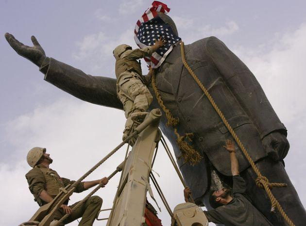 Un militar norteamericano coloca su bandera en la estatua de Sadam Hussein en Bagdad, en abril de 2003,...