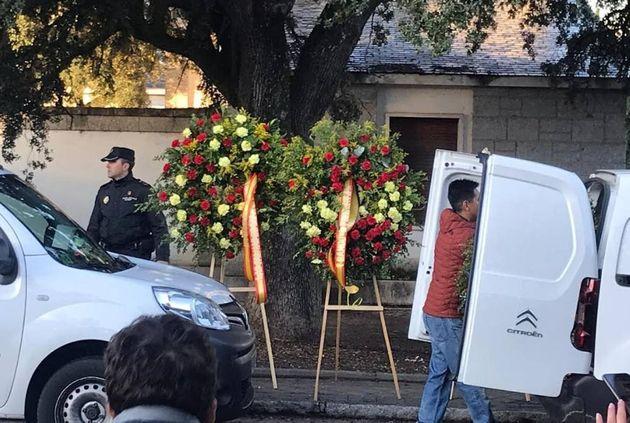 Operarios introducen coronas de flores en el cementerio de