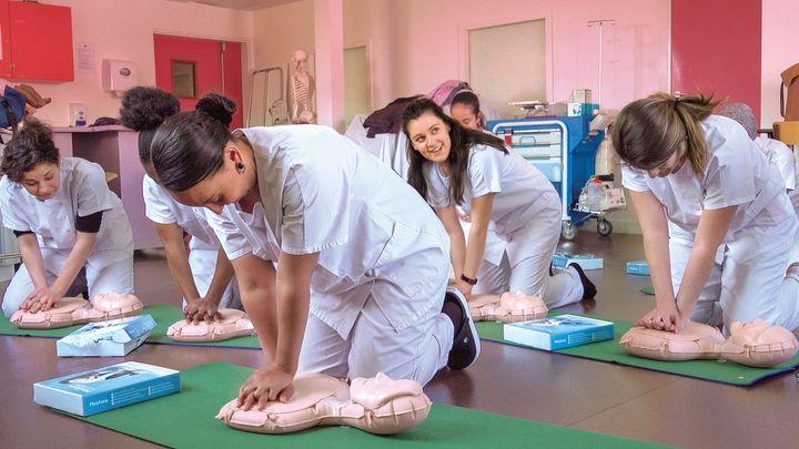 心臓マッサージの練習をする学生たち。「スタート!」の掛け声で、練習用の人形の胸を一斉に押し始める