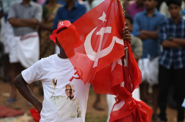 A supporter of the Communist Party of India (Marxist) carries a party flag at an election campaign rally...