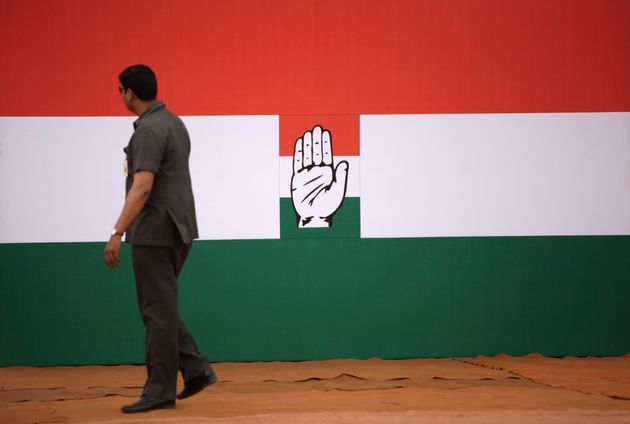 An Indian security man walks near a Congress party symbol in this file