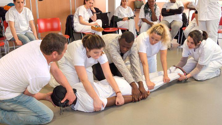 担架に乗せるための練習。うつ伏せの患者の体を、5人がかりで仰向けにする