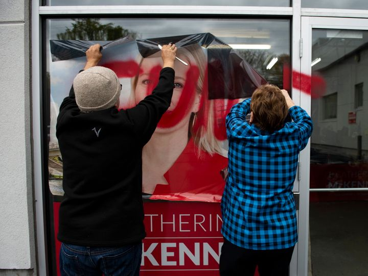 Campaign team members remove a defaced window decal from a window of Liberal MP Catherine McKenna's campaign office, on Wednesday, Oct. 24, 2019.