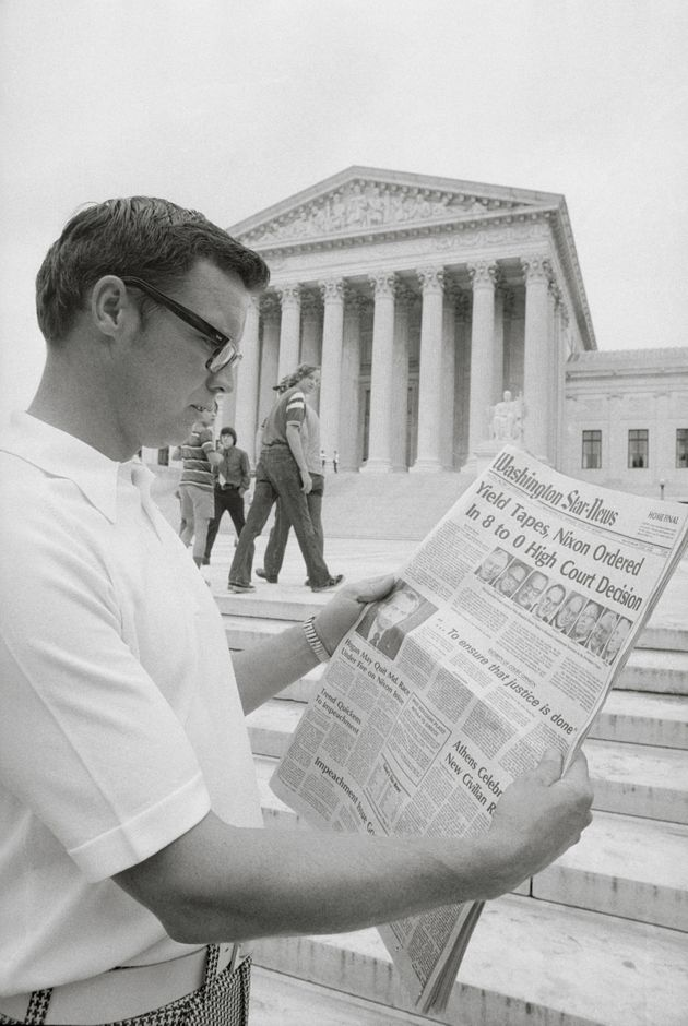 A visitor in the nation's capital reads the headlines in 1974 in front of the Supreme Court telling of...