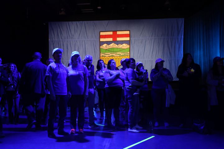 Supporters stand in front of the Alberta flag at the United Conservative Party election night headquarters in Calgary on April 16, 2019.