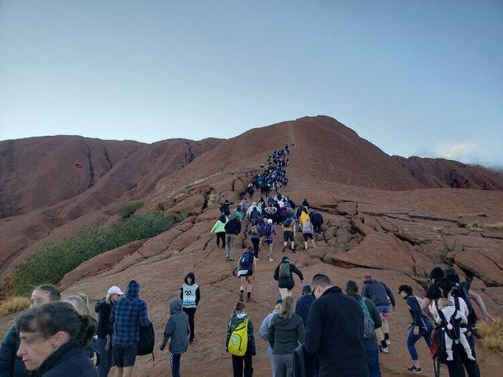 Tourists crowd a trail as they attempt to climb the Uluru