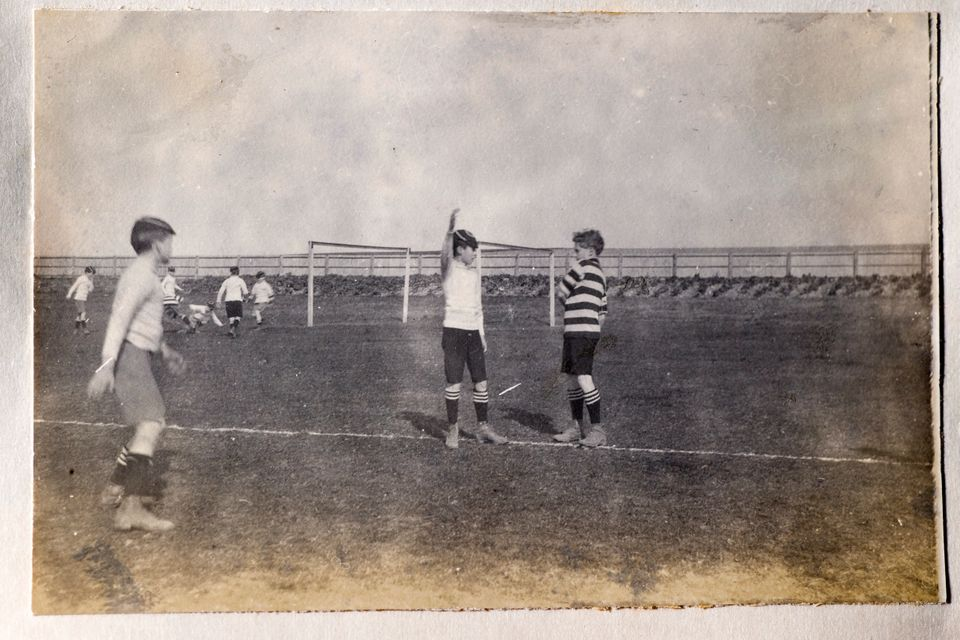 Vintage photograph of a group of boys playing football. From the late victorian or early edwardian