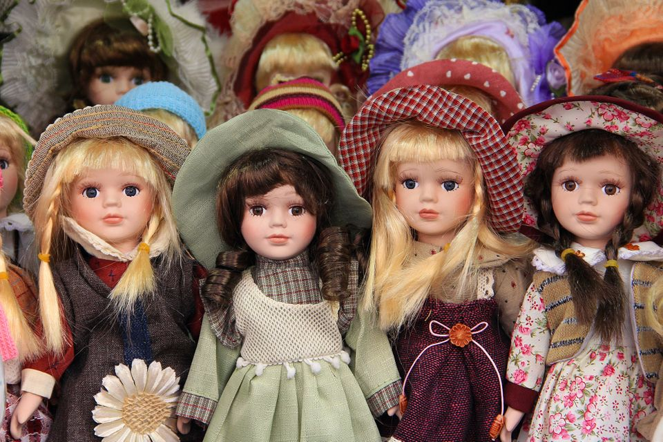 Porcelain dolls for children, dressed withcolorful hats and dresses in Prague market, sold as
