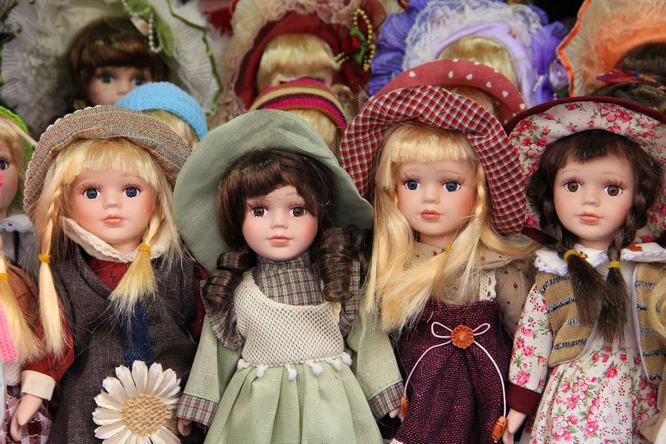 Porcelain dolls for children, dressed withcolorful hats and dresses in Prague market, sold as souvenirs.