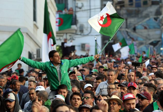 Demonstrators carry national flags during a protest against the country's ruling elite and rejecting...