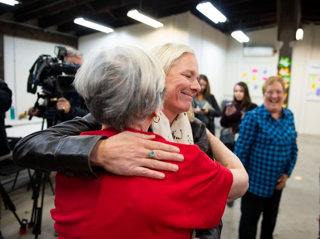 MP Catherine McKenna hugs a member of her team after speaking to reporters after a misogynistic slur was spray painted on her campaign office in Ottawa, on Thursday, Oct. 24, 2019.