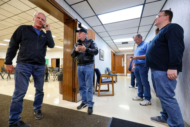 Officials of UAW Local 160 check their phones to get updates on the UAW-GM contract ratification vote...
