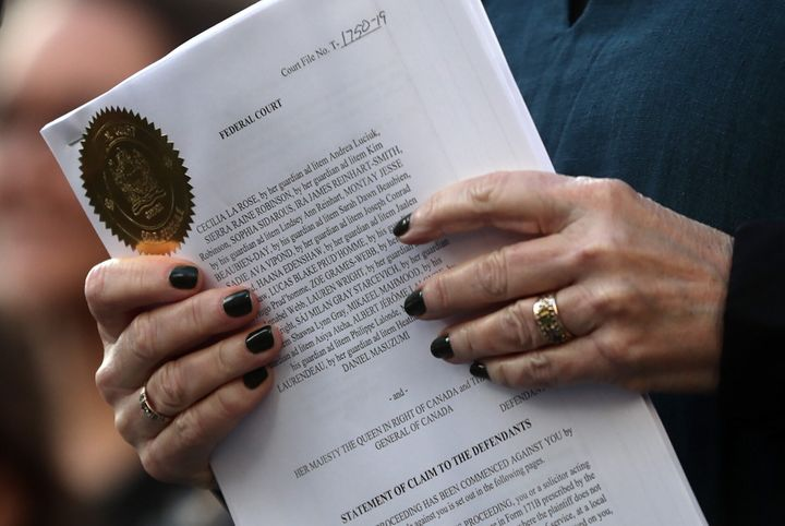 A lawyer holds the documents filed on behalf of the 15 young people who are parties to a lawsuit against the federal government for contributing to high levels of greenhouse gas emissions and dangerous climate change during a rally in Vancouver on Friday.