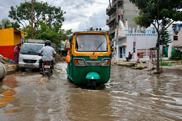 An auto-rickshaw wades through a flooded street in Bangalore after rain showers on October 24,