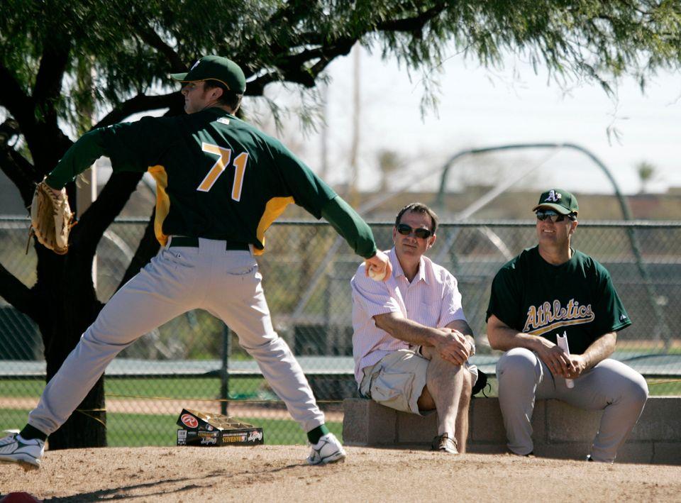 Oakland Athletics' general manager Billy Beane, center, and manager Bob Geren, right, watch as pitcher...