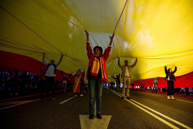 Simpatizantes de Vox sostienen una bandera gigante de