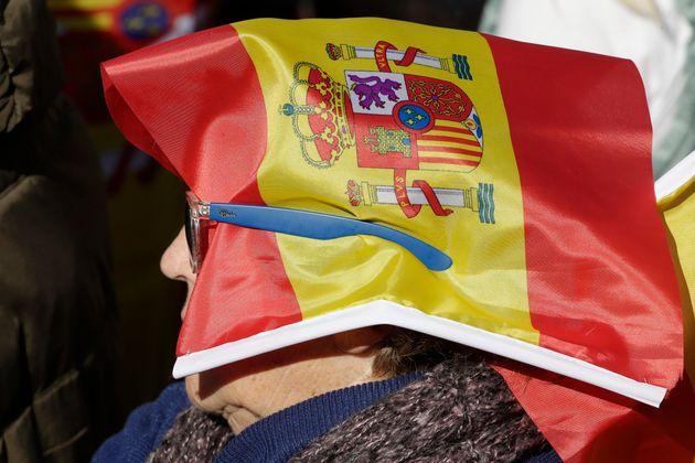 Una mujer sujeta con sus gafas la bandera de España que le sirve para no estar con la cara al
