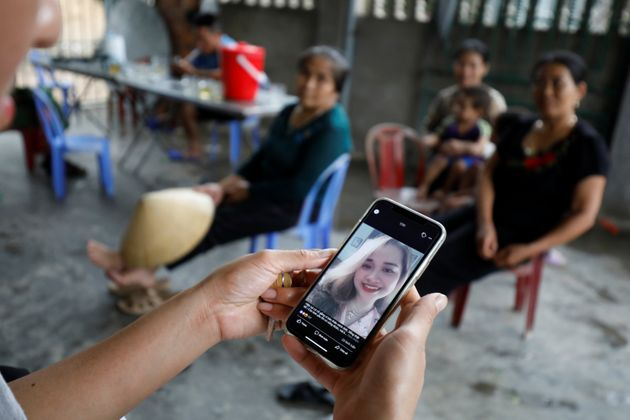 A relative looks at an image of Anna Bui Thi Nhung, a Vietnamese suspected victim in a truck container...