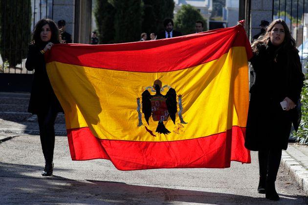 Dos familiares de Franco salen del Valle de los Caídos con una bandera