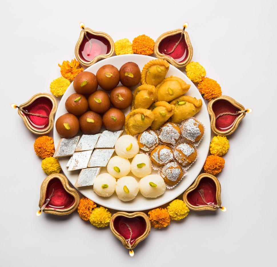 Plate full of gulab jamun, rasgulla, kaju katli, motichoor/bundi laddu, gujiya or karanji.