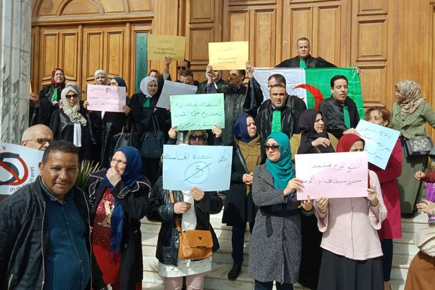 Algerian judges hold placards as they protest against their ailing president's bid for a fifth term in...