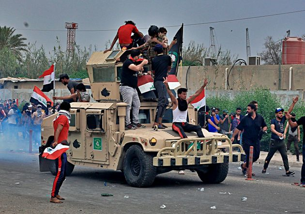 Protesters ride an Iraqi Army armored vehicle during a demonstration in Basra, Iraq, Friday, Oct. 25,...