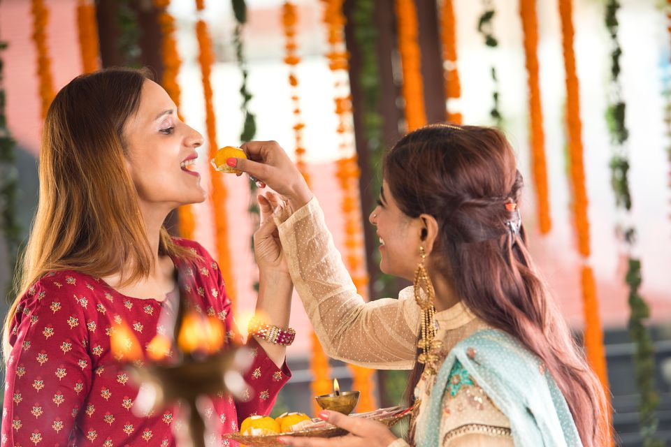 Indian woman feeding sweet food to her sister-in-law on the occasion of traditional