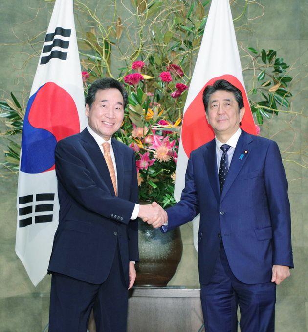 韓国の李洛淵首相(左)と握手する安倍晋三首相。会談の中で、安倍首相は韓国大法院の判決を「国際法に明確に違反」などと述べた=10月24日、首相官邸