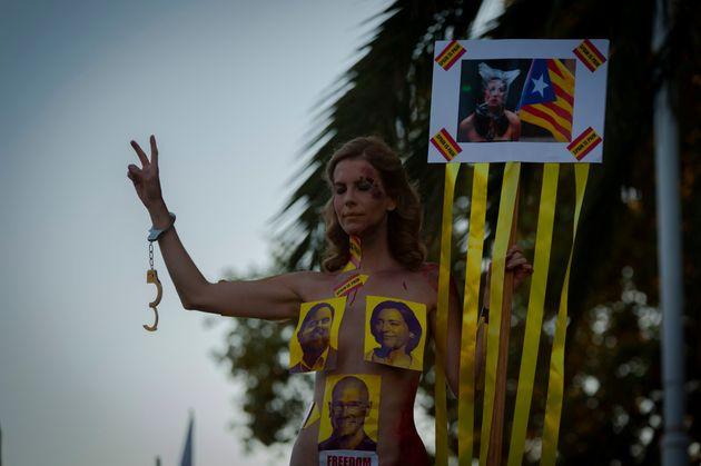 Una mujer protesta desnuda, tapada con algunas imágenes de los políticos catalanes presos,...