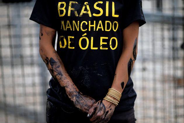 Ativista do Greenpeace protesta pela demora das autoridades brasileiras em reagir ao vazamento de óleo...