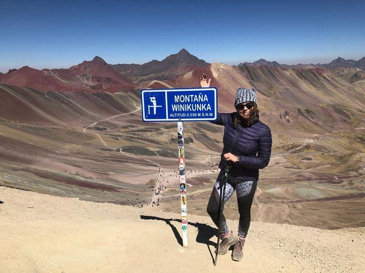 La autora en la cima de la montaña de colores en Perú.