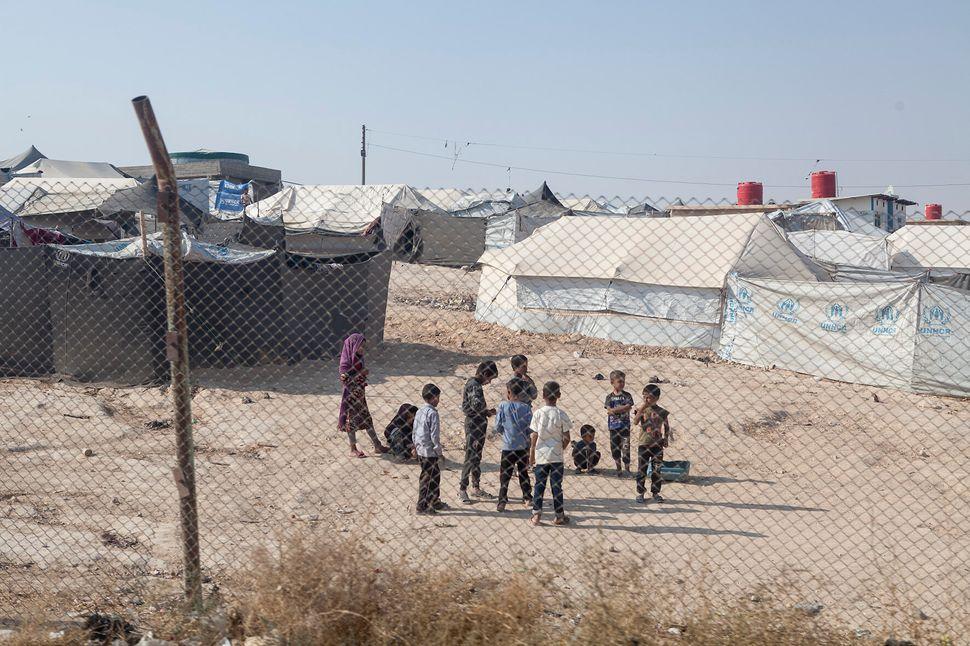 Al Hol Camp, un gruppo di bambini sfollati sono radunati vicino alla recinzione perimetrale del