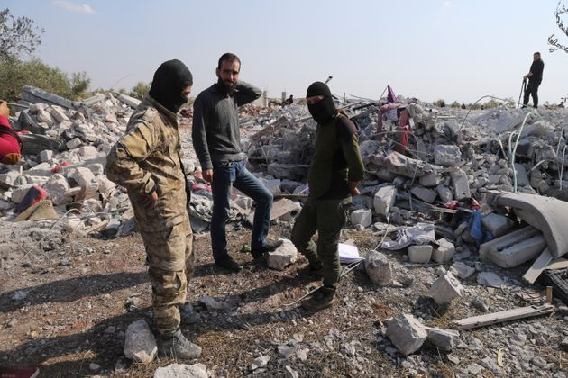People look at a destroyed houses near the village of Barisha, in Idlib province, Syria, Sunday, Oct....