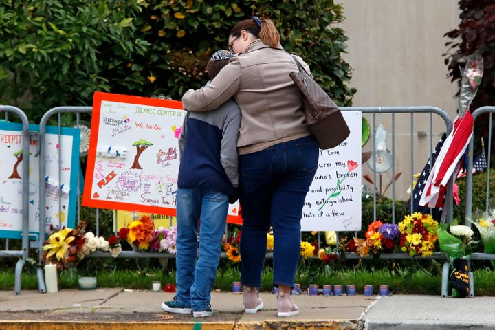 A mother hugs her son in front of a memorial at the Tree of Life synagogue in Pittsburgh on Sunday, Oct. 27, 2019, the first