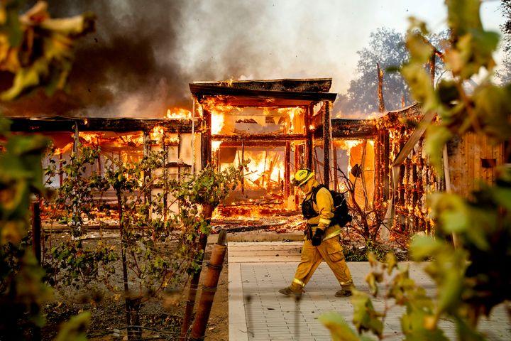 Woodbridge firefighter Joe Zurilgen passes a burning home as the Kincade Fire rages in Healdsburg, Calif., on Sunday, Oct 27,