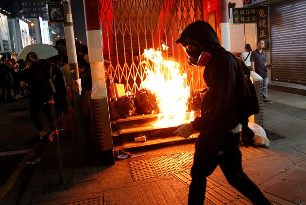 An anti-government protester walks past a burning barrier outside Mong Kok MTR station during a protest...