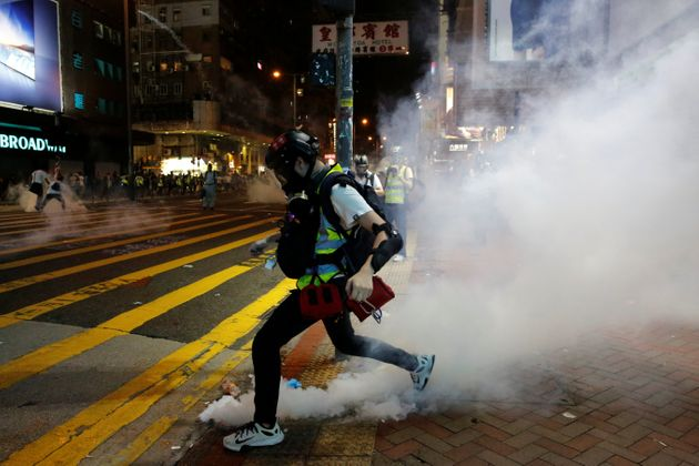 A first aid volunteer kicks a tear gas canister during an anti-government protest at Mong Kok in Hong...