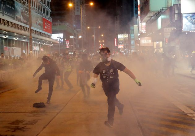 A demonstrator runs to throw back a tear gas canister to riot police during an anti-government protest...