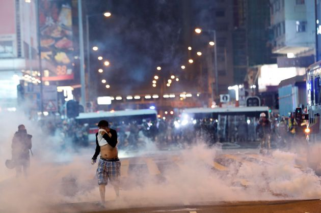 A man runs among the tear gas during a protest in Hong Kong's tourism district of Tsim Sha Tsui, China...