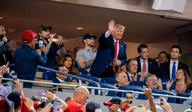 US President Donald Trump (C) waves as US First Lady Melania Trump looks on as they watch Game 5 of the...