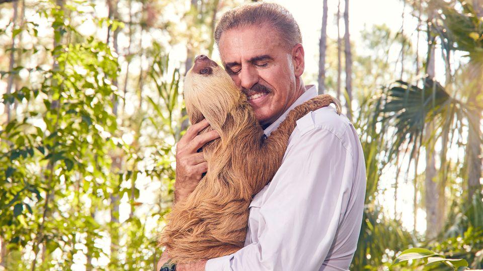Ron Magill, do Zoo de Miami, curte o abraço de uma preguiça-de-dois-dedos chamada
