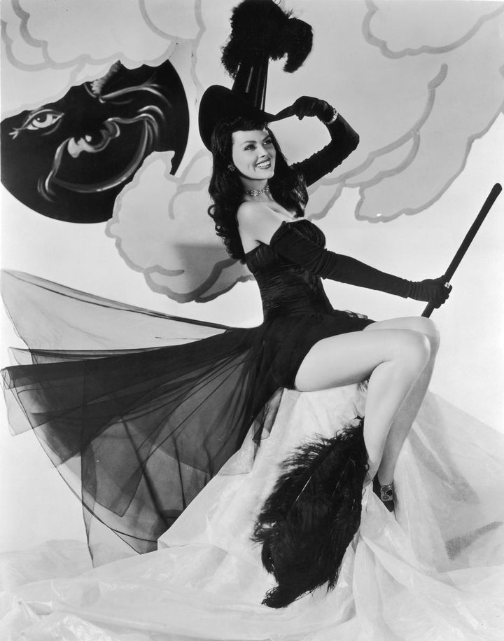Actress Dusty Anderson poses in a witch's hat and a strapless chiffon costume while holding a feathered broom for Columbia Pictures in the 1940s.