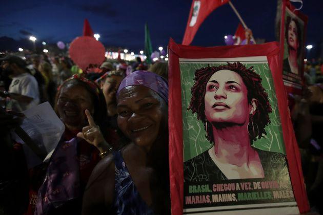 Mulher leva um pôster com a imagem da vereadora Marielle Franco durante manifestação...